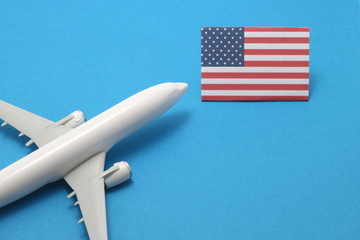 Miniature airplane flies toward the flag of United States of America.