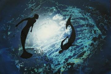 Two mermaids circling underwater.
