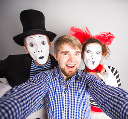 A young man and Funny couple of mimes taking a selfie photo