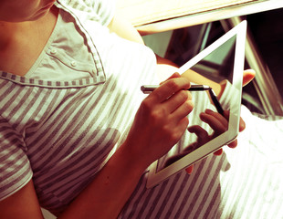 Girl in a striped shirt with a tablet computer and a stylus. Soft and sunny. With reflection. Retro effect.