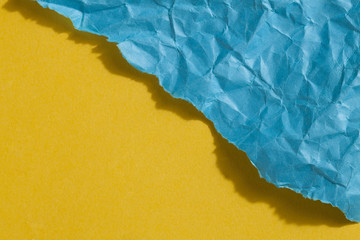 blue wrinkled and ripped paper on a taut yellow paper