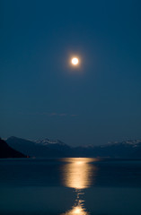 Full moon above snow-clad mountains reflected in a Norwegian fjord