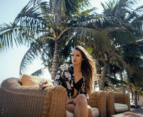 young pretty woman at swimming pool relaxing in chair, fashion look lingerie at hotel close up smiling cool vacations summer