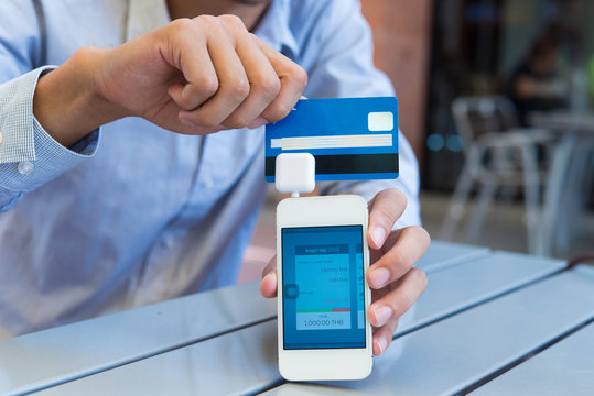 Businessman Swiping Credit Cards on Mobile Phone, payment is easy for customers