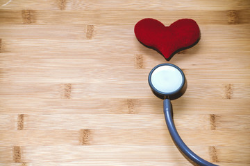 Red heart and a stethoscope on wood background. take care of heart Concept.
