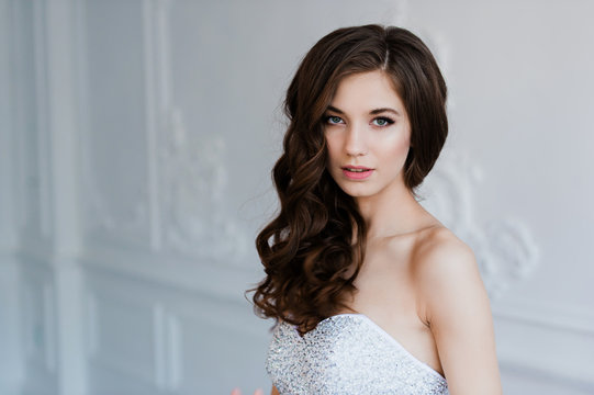 Close portrait of beautiful smiling bride woman with long curly hair posing in wedding dress at interior and smiling. Beauty indoor portrait.