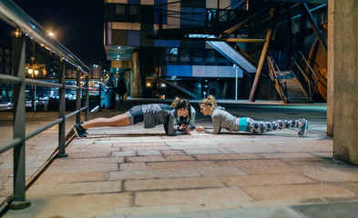 Two women doing stretching after running