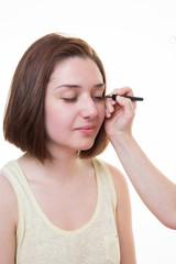 Make-up artist applying liquid eyeliner with brush, close up