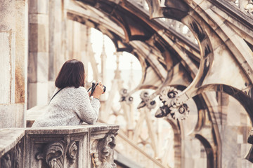Tourist woman with camera on the Milan Cathedral roof