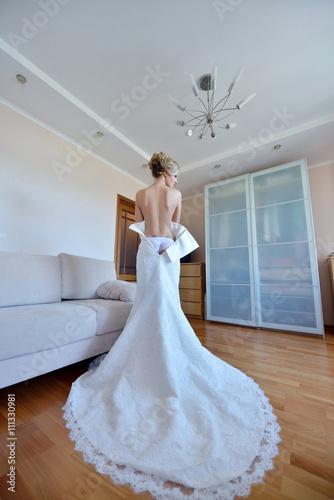 Beautiful bride in lingerie is wearing a wedding dress. Beauty model ...