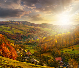 village falls on hillside with autumn forest in mountain at suns