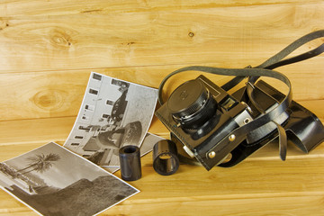 Old film camera in cover, photos and film on a wooden surface