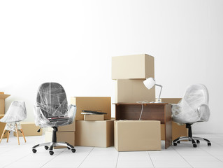 Moving cardboard boxes and personal belongings in empty office space