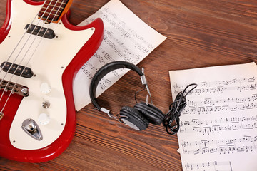 Electric guitar with headphones and notes on wooden background