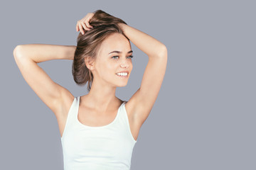 Beautiful girl holds her hair and smiling