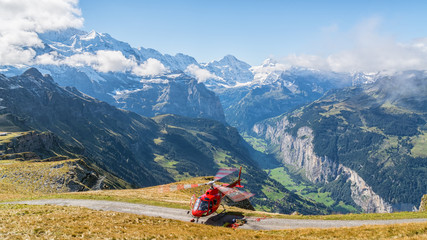 Panoramic view of red helicopter with spectacular landscape at background
