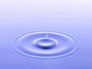 single water drop falling into blue water
