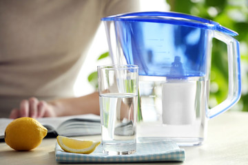 Water filter jug with lemon, glass and reading woman on background