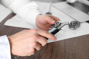 Male hands measuring metal detail closeup