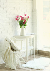 Beautiful tulips on white wooden table