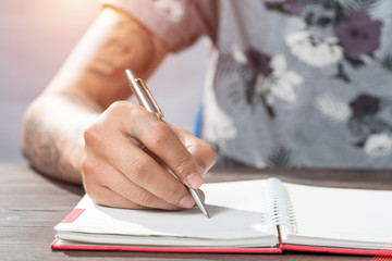 Male hand with pen writing on the notebook.