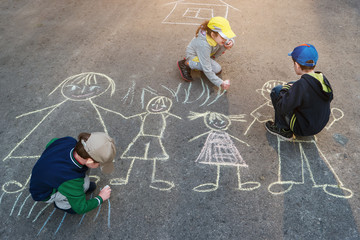 Children is drawing sun on asphalt in spring park.