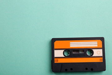 Old audio cassette on turquoise background