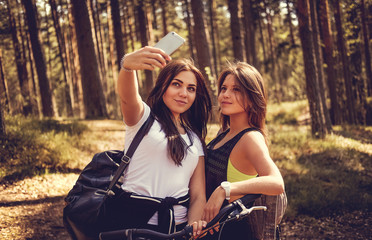 Two female with bicycles making selfie in summer forest.