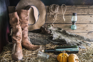 Still life photography with traditional leather boots and american west rodeo brown cowboy hat in vintage ranch barn background