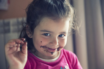 Madrid, Spain, three years girl eating chocolate, dirty mouth