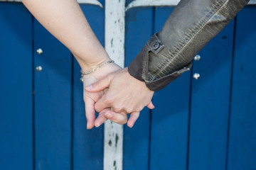 Lovely hands of couple holding hands over blue background