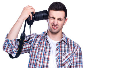 Shoot yourself by camera. A young attractive photographer pressing his camera against his ear.