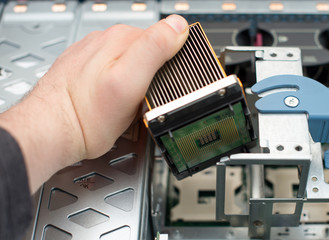 Computer technician installing CPU into motherboard.