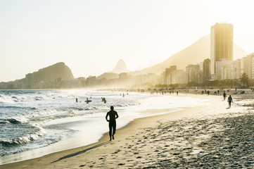 Silhouettes walking in front of golden sun setting behind the Rio de Janeiro skyline at the Leme end of Copacabana Beach