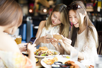 happy friends with smart phones taking picture of food