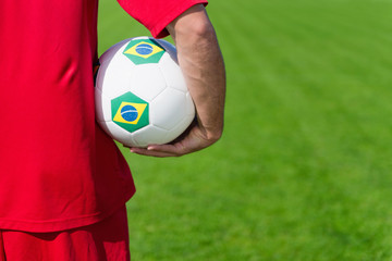 Soccer player on the field, holding ball with Brazilian flags. Convenient space for copy