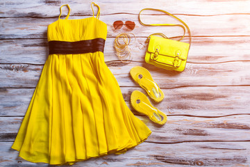 Yellow dress, sunglasses and bag. Casual dress with bright accessories. Girl's summer outfit idea. Fashionable clothing in stock.