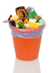 Bucket filled with household waste and food isolated on white.
