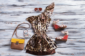 Leopard dress and wedge sandals. Asymmetric dress with bicolor purse. Designer dress on wooden showcase. Luxury and beauty.