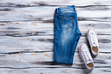 Blue jeans and white keds. Folded denim pants and shoes. Casual footwear on wooden floor. Last items in stock.