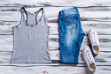 Gray tank top and jeans. White shoes with tank top. Girl's casual outfit for summer. Discounted merchandise in fashion store.