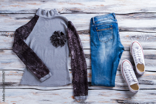 Gray top with black sleeves. sweatshirt jeans and white shoes