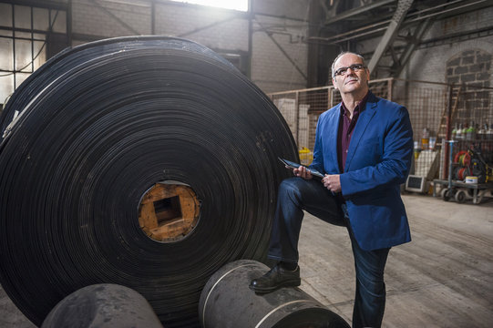 Factory foreman standing next to industrial roll of rubber