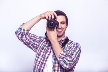 Say cheese! Young man focusing at you with digital camera while standing in studio on gray background