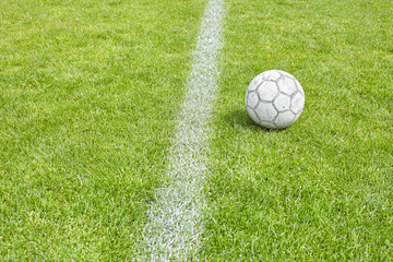 Used soccer ball on grass by a sideline, shallow depth of field.