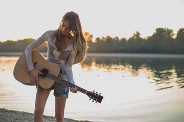 Girl holding down guitar on the beach