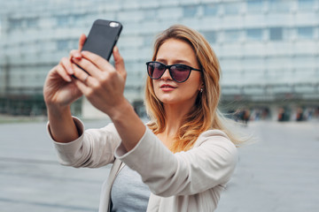 Girl taking selfie. Urban background.