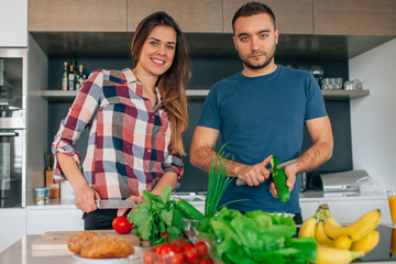 Young couple preparing salad in the kitchen. They are cutting to