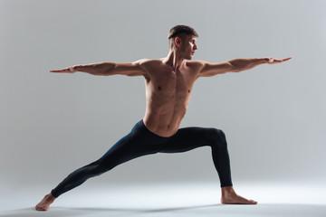 Full length portrait of a man doing yoga exercises