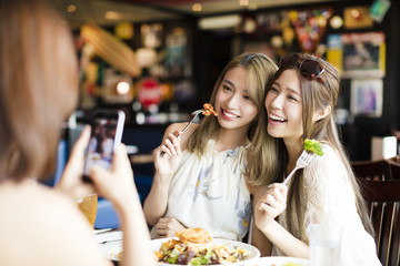 happy friends with smart phones taking picture in restaurant